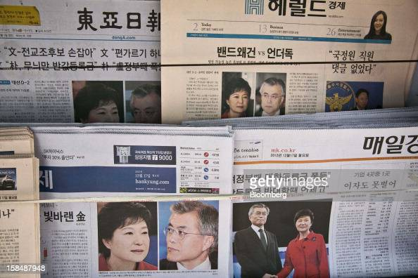 Newspapers reporting on South Korean presidential candidates Park Geun Hye from the ruling New Frontier Party in red and Moon Jae In from the main...