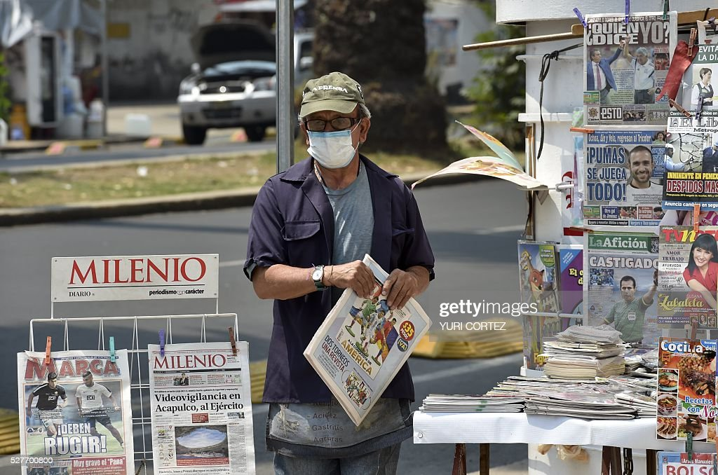 A newspapers vendor wears a surgical mask in smog-covered Mexico City on May 3, 2016 Mexico City officials issued a new air pollution alert yesterday, meaning that 40 percent of vehicles will be banned on Tuesday, while industries will be required to cut emissions. The alarm was raised after ozone levels reached 161 points, above the 150 level. The threshold was lowered from 190 to 150 last month. / AFP / YURI