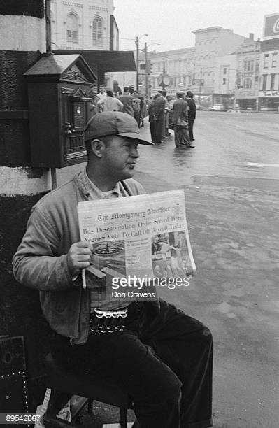 A newsvendor holds up a copy of the Montgomery Advertiser which features a headline about the bus boycott Montgomery Alabama December 1956