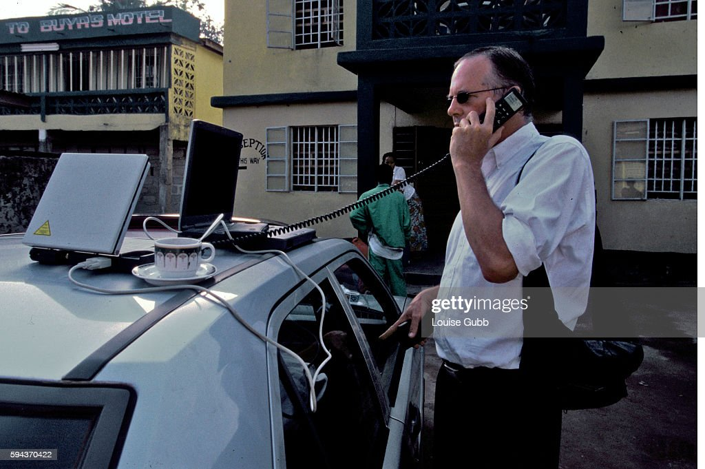 Newsweek journalist Tom Masland in Sierra Leone communicating with the Newsweek office in New York via his satellite phone outside a hotel he stayed...