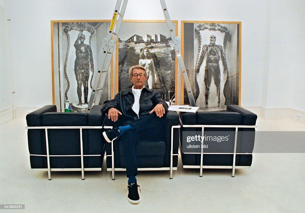 Newton, Helmut *-+(Eigentlich Helmut Neustaedter)Fotograf, Australien- Ganzkoerperaufnahme, vor eigenen Fotografien in einem Ausstellungsraum sitzend- 1999