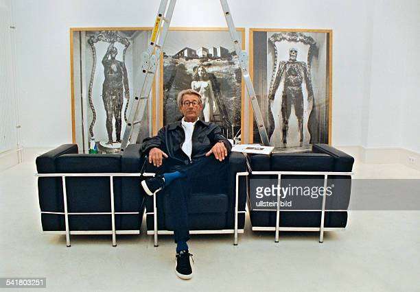 Newton Helmut *Fotograf Australien Ganzkoerperaufnahme vor eigenen Fotografien in einem Ausstellungsraum sitzend 1999