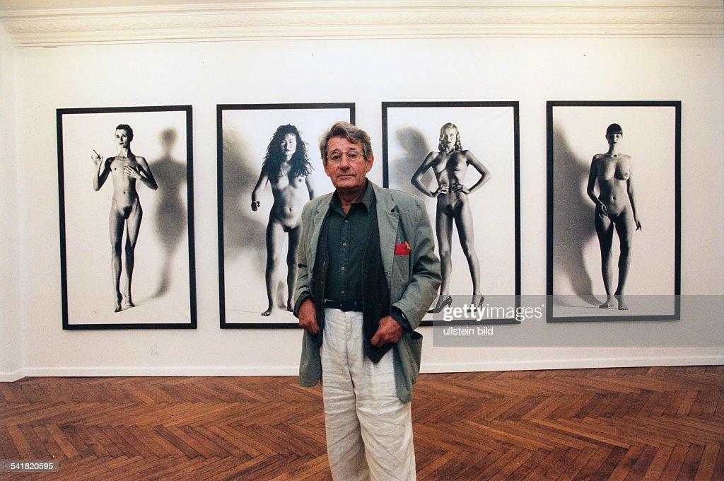 Newton, Helmut *-+(Eigentlich Helmut Neustaedter)Fotograf, Australien- Halbportrait, vor Fotos seiner Ausstellung 'Big Nudes'- 1995