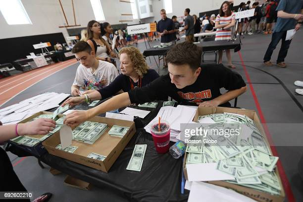 Newton North student Henry Johnson right teacher Ellen Novinsky center and student Matteo Greenberg work the desk with fake cash at the Newton North...