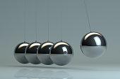 Newton's Cradle, shiny, metallic balancing balls, pendulum.