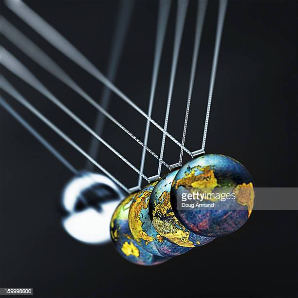 Newtons Cradle made of metal Earth globes