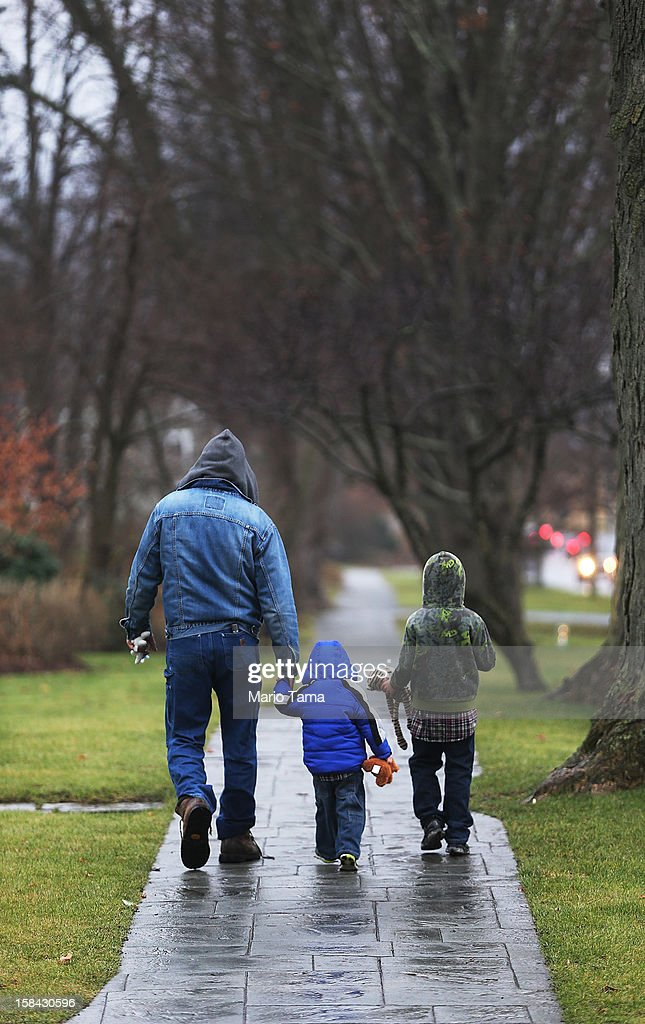 Newtown resident Palmer Chiaepetta walks with his sons Jonathan, 2, and Jackson, 8, two days after the mass shooting at Sandy Hook Elementary School on December 16, 2012 in Newtown, Connecticut. Twenty six people were shot dead, including twenty children, after a gunman identified as Adam Lanza in news reports opened fire in the school. Lanza also reportedly had committed suicide at the scene.