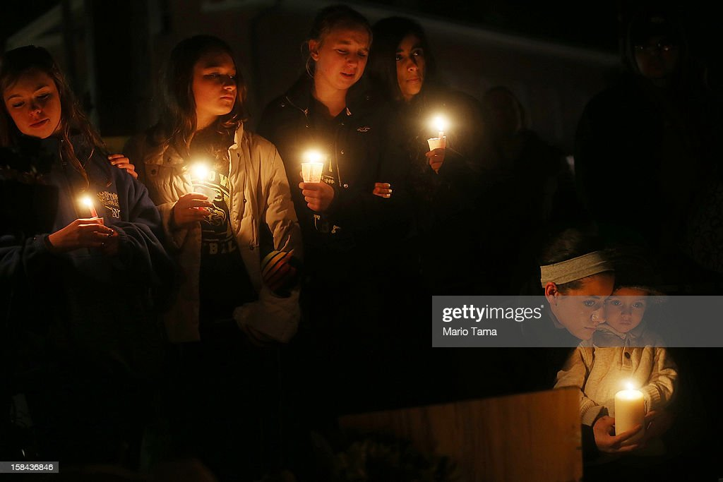 Newtown residents Claire Swanson, Kate Suba, Jaden Albrecht, Simran Chand and New London, Connecticut residents Rachel Pullen and her son Landon DeCecco, hold candles at a memorial for victims on the first Sunday following the mass shooting at Sandy Hook Elementary School on December 16, 2012 in Newtown, Connecticut. U.S. President Barack Obama visited the grief stricken town today.