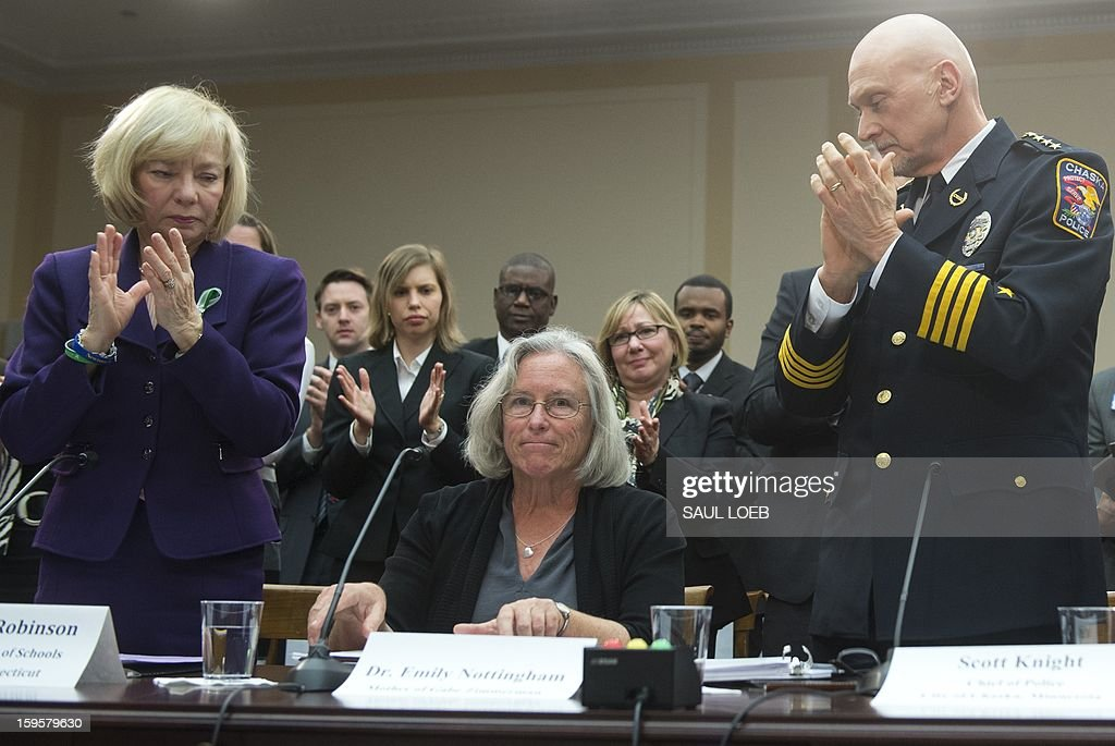 Newtown School Superintendent Janet Robinson (L) and Police Chief Scott Knight (R) of Chaska, Minnesota, applaud Emily Nottingham (C), mother of Congressional staffer Gabe Zimmerman who was killed during the shooting attack on former US Representative Gabrielle Giffords, after speaking about gun violence during a meeting of the House Democratic Steering and Policy Committee on Capitol Hill in Washington, DC, on January 16, 2013. AFP PHOTO / Saul LOEB