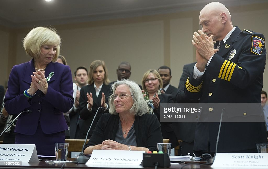 Newtown School Superintendent Janet Robinson (L) and Police Chief Scott Knight (R) of Chaska, Minnesota, applaud Emily Nottingham (C), mother of Congressional staffer Gabe Zimmerman who was killed during the mass shooting attack on former US Representative Gabrielle Giffords, after speaking about gun violence during a meeting of the House Democratic Steering and Policy Committee on Capitol Hill in Washington, DC, on January 16, 2013. AFP PHOTO / Saul LOEB