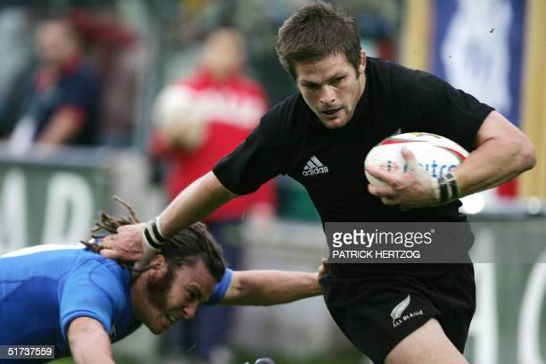 NewZealand flanker Richie McCaw runs in a try despite Italian Scrum Half Paul Griffen during a rugby union test match at Flaminio stadium in Rome The...