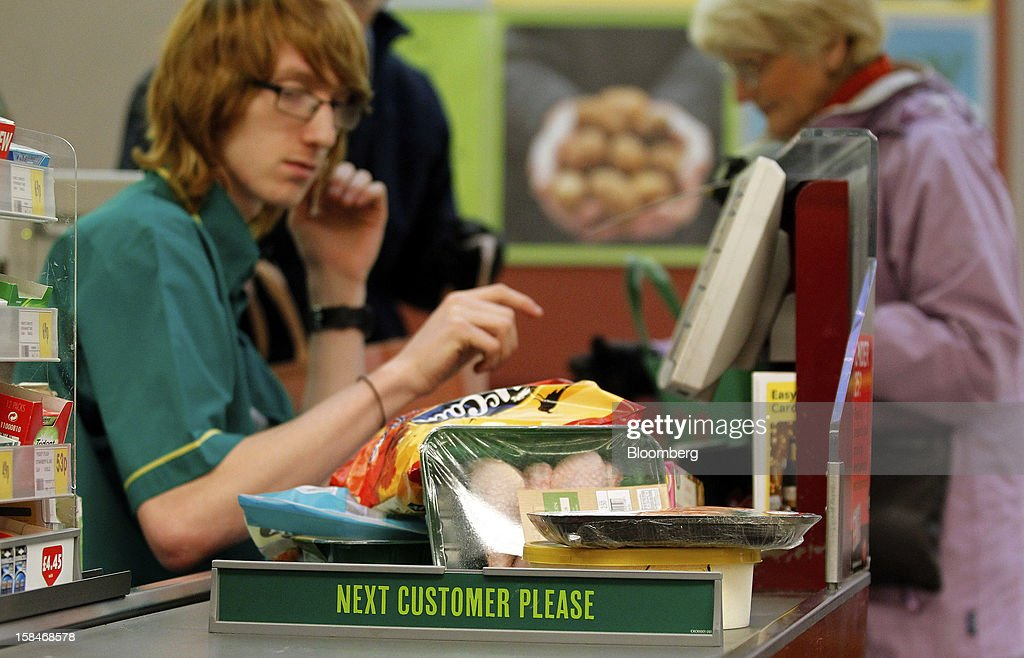 A 'Next Customer Please' sign sits on a checkout counter as an employee serves a customer inside a Morrisons supermarket, operated by William Morrisons Supermarkets Plc, in Chadderton, U.K., on Monday, Dec. 17, 2012. The British Christmas is the biggest epicurean occasion of the year, with households spending a total of 4 billion pounds on food in the final week before Dec. 25. Photographer: Paul Thomas/Bloomberg via Getty Images
