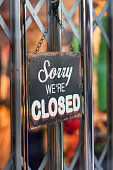 Sorry, we're closed sign hanged on the closed door. Dors ae secured wit metal rails. Nice colorful background.