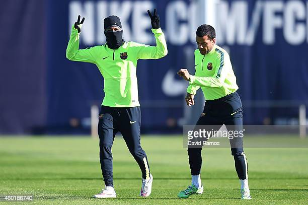 Neymar and Dani Alves of FC Barcelona share a joke during a training session ahead of their UEFA Champions League Group F match against Paris...