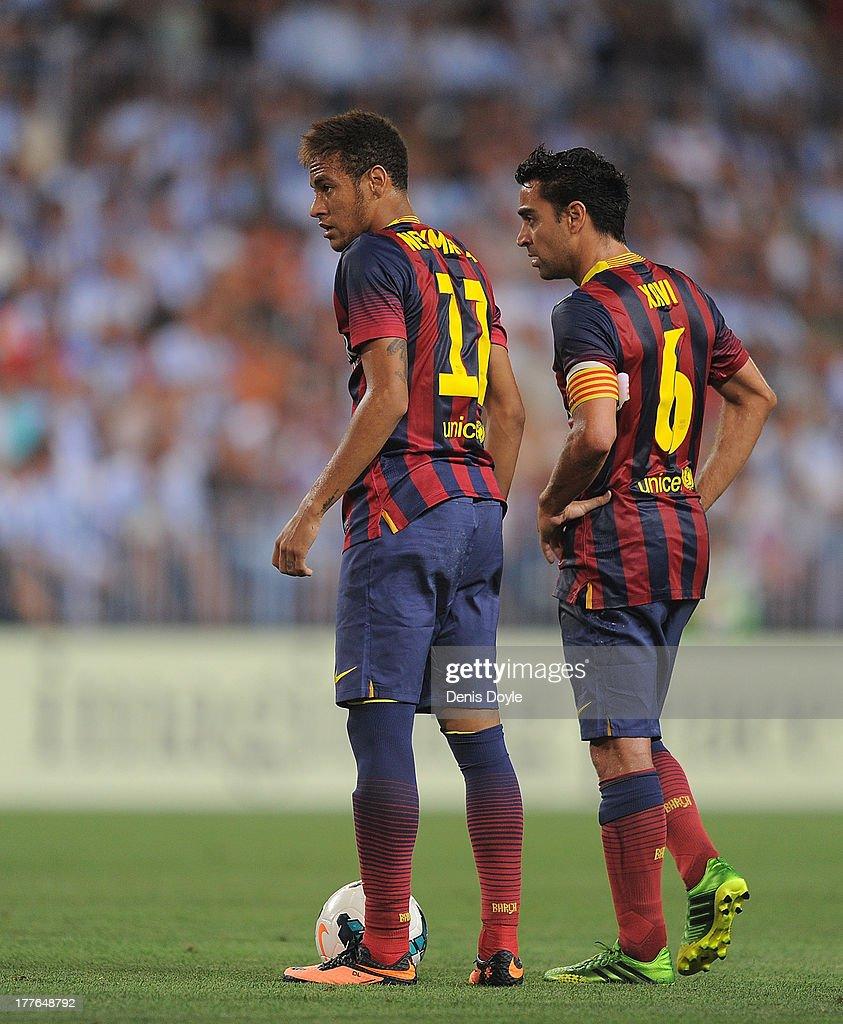 Neymar (L) and Xavi Hernandez of FC Barcelona line up a free kick during the La Liga match between Malaga CF and FC Barcelona at La Rosaleda Stadium on August 25, 2013 in Malaga, Spain.