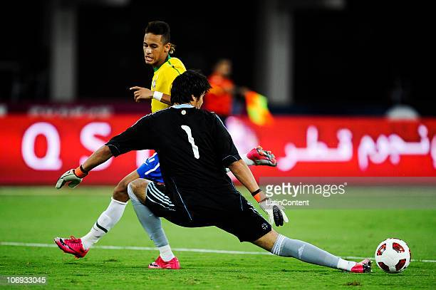 Neymar da Silva Santos Junior of Brazil tries to passes the ball through Sergio Romero of Argentina during their FIFA friendly match at Khalifa...