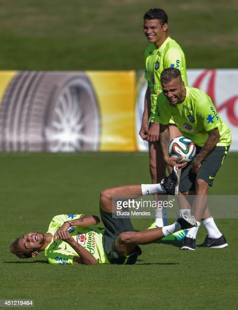 Neymar jokes with a Daniel Alves and Thiago Silva during a training session of the Brazilian national football team at the squad's Granja Comary...