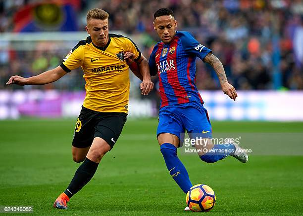Neymar JR of Barcelona competes for the ball with Ontiveros of Malaga during the La Liga match between FC Barcelona and Malaga CF at Camp Nou stadium...