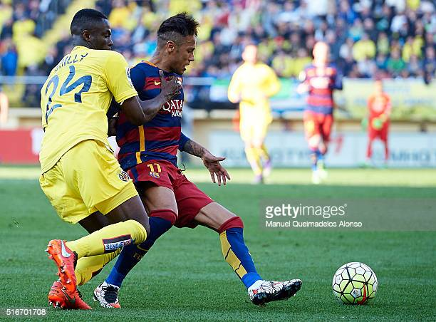Neymar JR of Barcelona is tackled by Eric Bertrand Bailly of Villarreal during the La Liga match between Villarreal CF and FC Barcelona at El...