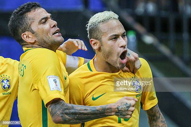 Neymar Jr of Brazil celebrates with teammate Dani Alves after scoring the second goal of his team during a match between Brazil and Colombia as part...