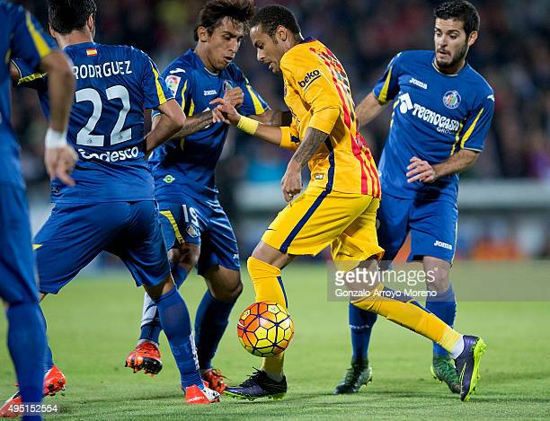 Neymar JR of FC Barcelona competes for the ball with Damian Suarez of Getafe CF and his team mate Victor Rodriguez during the La Liga match between...