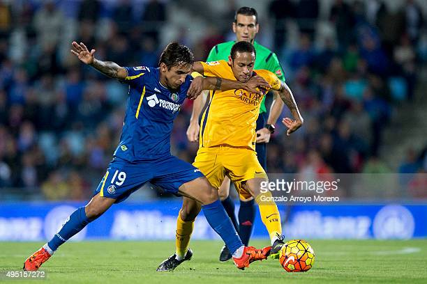 Neymar JR of FC Barcelona competes for the ball with Damian Suarez of Getafe CF during the La Liga match between Getafe CF and FC Barcelona at...