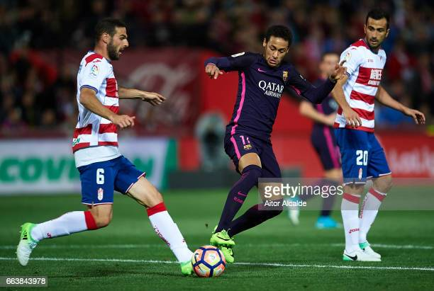Neymar Jr of FC Barcelona competes for the ball with David Rodriguez Lomban and Matthieu Saunier of Granada CF during the La Liga match between...