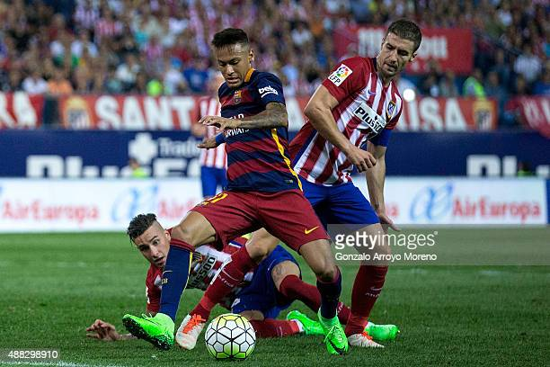 Neymar JR of FC Barcelona competes for the ball with Gabi Fernandez of Atletico de Madrid and his teammate Jose Maria Gimenez during the La Liga...