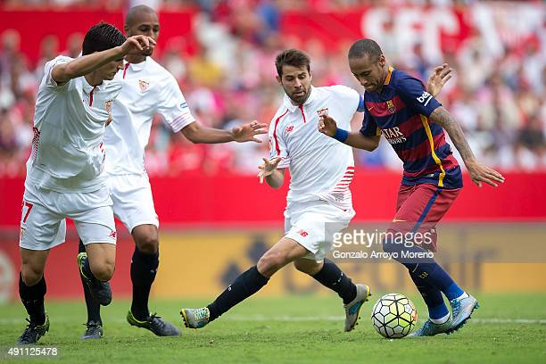 Neymar JR of FC Barcelona competes for the ball with Jorge Andujar Moreno alias Coke of Sevilla FC and his teammate Denis Suarez of Sevilla FC during...