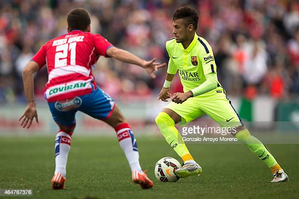 Neymar JR of FC Barcelona competes for the ball with Roberto Ibanez of Granada CF during the La Liga match between Granada CF and FC Barcelona at...