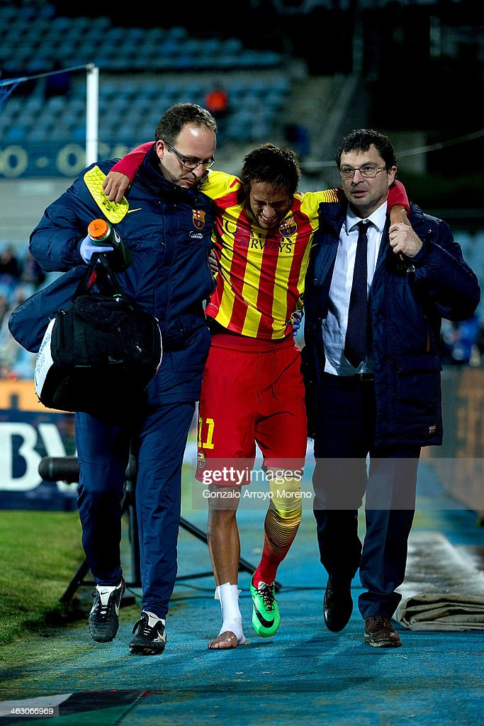 Neymar Jr of FC Barcelona is assisted as he leaves the pitch after picking up an injury during the Copa del Rey Round of 8 second leg match between...