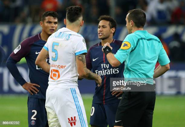 Neymar Jr of PSG argues with Lucas Ocampos of OM while referee Ruddy Buquet is about to give them both a yellow card and Thiago Silva of PSG looks on...