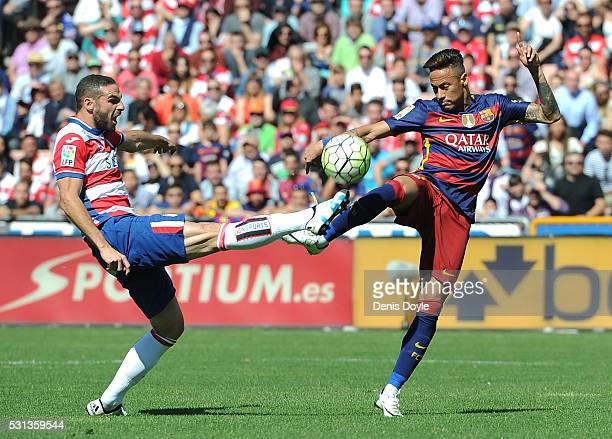Neymar of Barcelona and David Lomban of Granada compete for the ball during the La Liga match between Granada and Barcelona at Estadio Nuevo Los...