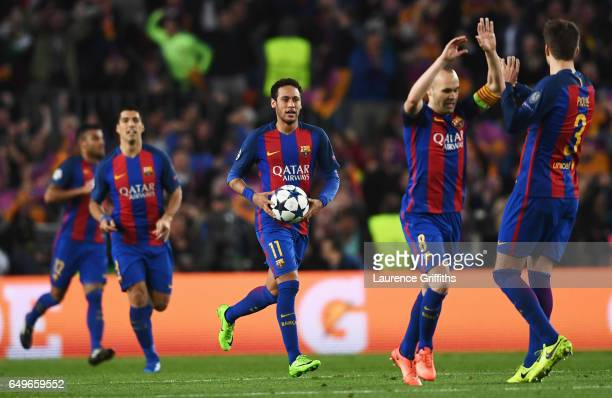 Neymar of Barcelona grabs the match ball as Barcelona players celebrate an own goal by Layvin Kurzawa of PSG for their second goal during the UEFA...