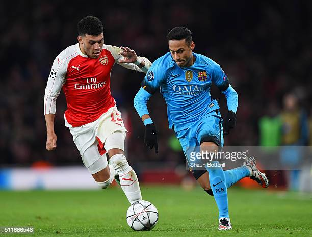 Neymar of Barcelona holds off the challenge from Alex OxladeChamberlain of Arsenal during the UEFA Champions League round of 16 first leg match...