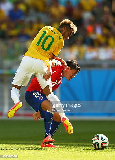 Neymar of Brazil and Charles Aranguiz of Chile compete for the ball during the 2014 FIFA World Cup Brazil round of 16 match between Brazil and Chile...