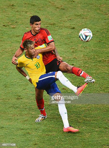 Neymar of Brazil and Francisco Javier Rodriguez of Mexico compete for the ball during the 2014 FIFA World Cup Brazil Group A match between Brazil and...