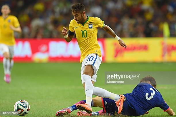 Neymar of Brazil and Gotoku Sakai of Japan compete for the ball during the international friendly match between Japan and Brazil at the National...