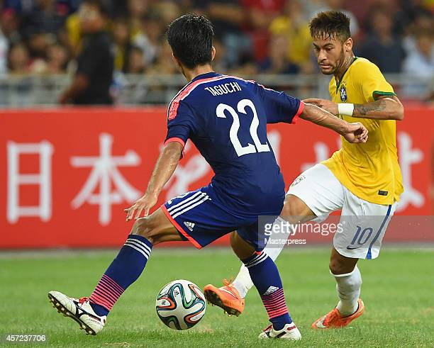 Neymar of Brazil and Taishi Taguchi of Japan compete for the ball during the international friendly match between Japan and Brazil at the National...