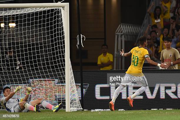 Neymar of Brazil celebrates his goal as Eiji Kawashima of Japan is seen in despair during the international friendly match between Japan and Brazil...
