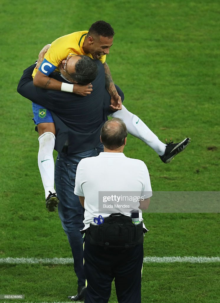 Neymar of Brazil celebrates with head coach Rogerio Micale as he opens the scoring during the Men's Football Final between Brazil and Germany at the...
