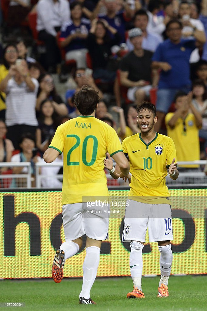 Neymar of Brazil (R) celebrates with Kaka after scoring a goal during the international friendly match between Japan and Brazil at the National Stadium on October 14, 2014 in Singapore.