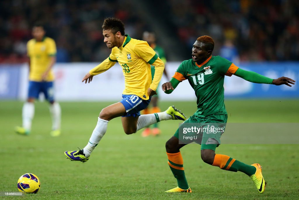 Neymar of Brazil (Center) competes the ball with Chongo Kabaso of Zambia (Right) during the international friendly match between Brazil and Zambia at Beijing National Stadium on October 15, 2013 in Beijing, China.