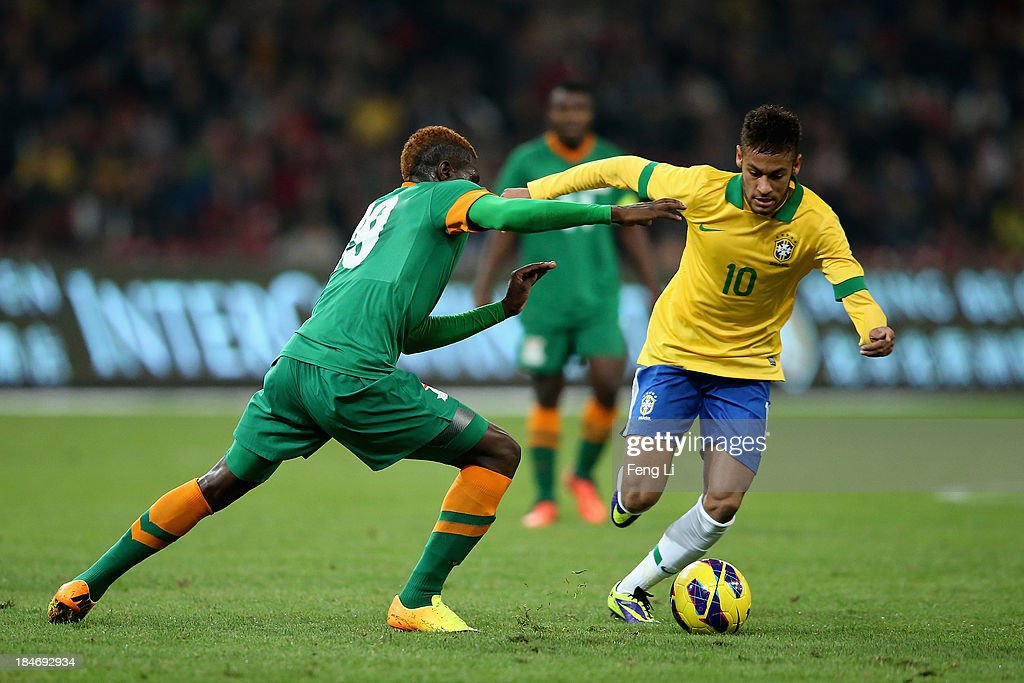 Neymar of Brazil (Right) competes the ball with Chongo Kabaso of Zambia (Left) during the international friendly match between Brazil and Zambia at Beijing National Stadium on October 15, 2013 in Beijing, China.
