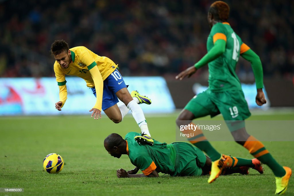 Neymar of Brazil (Left) competes the ball with Himonde Hichani (Bellow) and Chongo Kabaso (Right) of Zambia during the international friendly match between Brazil and Zambia at Beijing National Stadium on October 15, 2013 in Beijing, China.