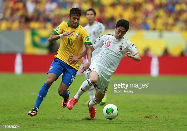 Neymar of Brazil competes with Shinji Kagawa of Japan during the FIFA Confederations Cup Brazil 2013 Group A match between Brazil and Japan at...
