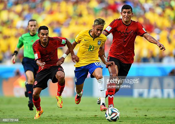 Neymar of Brazil controls the ball against Jose Juan Vazquez and Francisco Javier Rodriguez of Mexico during the 2014 FIFA World Cup Brazil Group A...