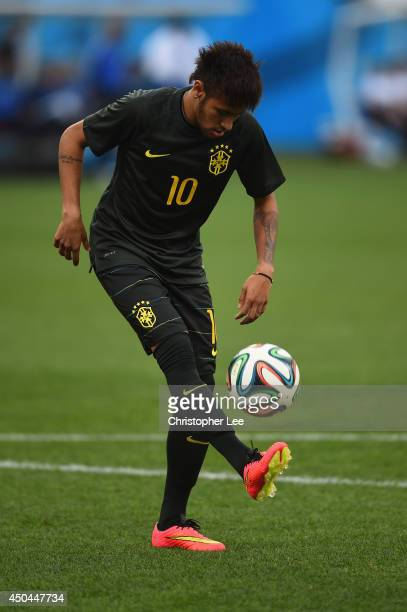 Neymar of Brazil controls the ball during a Brazil training session ahead of the 2014 FIFA World Cup Brazil opening match against Croatia at Arena de...