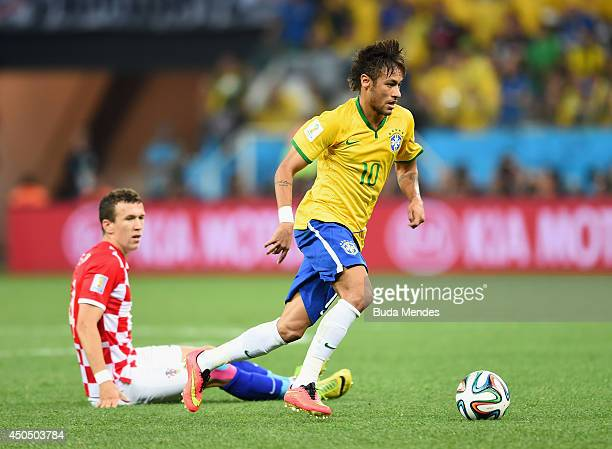 Neymar of Brazil dribbles past Ivan Perisic of Croatia in the first half during the 2014 FIFA World Cup Brazil Group A match between Brazil and...