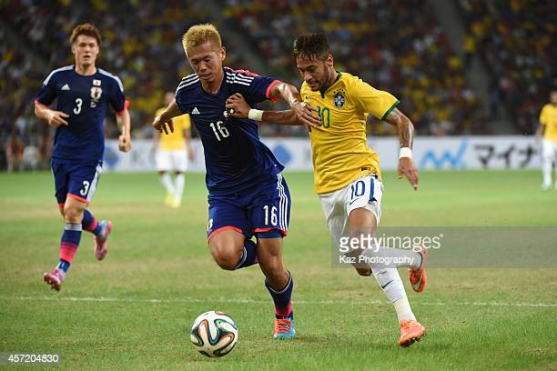 Neymar of Brazil dribbles the ball under the pressure from Tsukasa Shiotani of Japan during the international friendly match between Japan and Brazil...